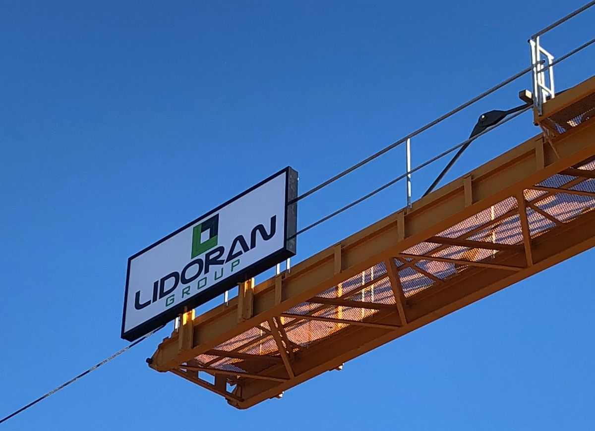 Industrial crane equipment in blue sky with Lidoran Group sign